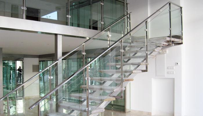 baranda interior con balaustres de base cuadrada combinados con paneles de cristal